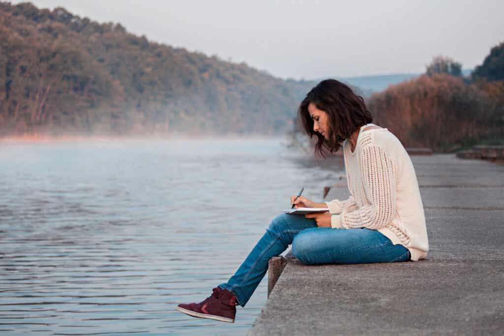Femme qui écrit près d'un lac.