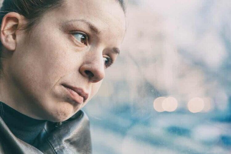 Une femme triste qui regarde par la fenêtre.
