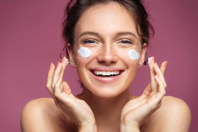 Une femme qui se met de la crème sur le visage.