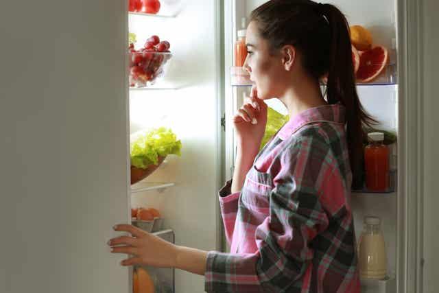 Une femme devant un frigo ouvert.