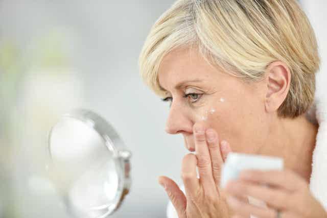 Une femme âgée qui se met de la crème sur le visage.